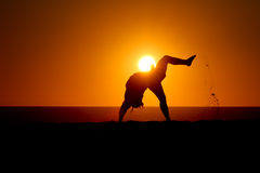 Silhouette of gymnast on beach at sunset Stock Photography
