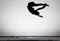 Silhouette of gymnast on trampoline Stock Photo