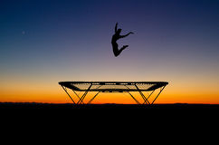 Silhouette of gymnast on trampoline in sunset Royalty Free Stock Photography