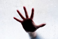 Silhouette of hand behind glass. Silhouette of hand behind wet glass Stock Image