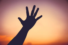 Silhouette of a hand on colorful sunset sky background. Stock Images