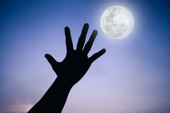 Silhouette of a hand with full moon on fantastic sky background. Stock Image