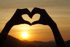 Silhouette hand gesture feeling love during sunset Royalty Free Stock Photos