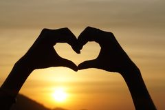 Silhouette hand gesture feeling love during sunset Stock Image