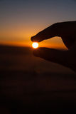 Silhouette of Hand Gripping the Sun Royalty Free Stock Photography
