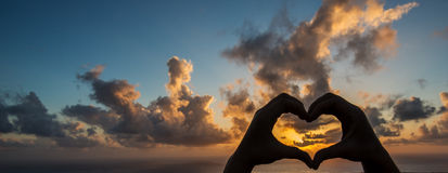 Silhouette hand in heart shape and beautiful sky. One-body creates heart symbol with help of hands. Heart symbol against beautiful sunset background Stock Image