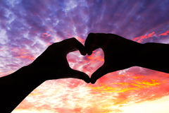 Silhouette hand in heart shape and beautiful sky Royalty Free Stock Photo