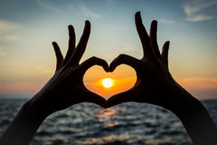 Silhouette hand heart shape. Heart hand shape with sunset background Royalty Free Stock Images