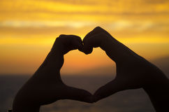 Silhouette of hand in heart shape on sunset Royalty Free Stock Photo