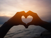 Silhouette hand in heart shape. Stock Images