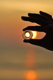 Silhouette hand hold round ice and sunset Royalty Free Stock Photos