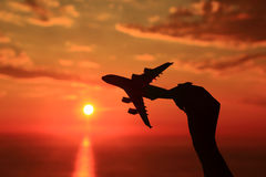 Silhouette of hand holding airplane Royalty Free Stock Photography