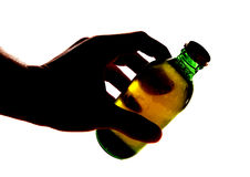 Silhouette of hand holding bottle of larger. Cutout Royalty Free Stock Image