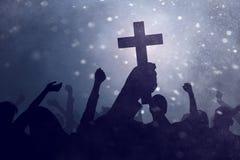Silhouette hand holding christian cross stock image