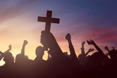 Silhouette hand holding christian cross. Image of silhouette hand holding christian cross, with people background Stock Photos