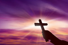 Silhouette of hand holding christian cross royalty free stock images