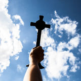 Silhouette of Hand holding cross in the sky, focus at the cross Royalty Free Stock Photos