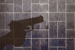 Silhouette of a hand holding a gun. On dirty glazed tiles Royalty Free Stock Images