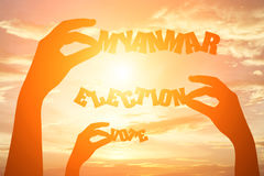 Silhouette of hand holding paper cut text MYANMAR ELECTION VOTE Stock Images