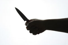 Silhouette hand with a knife Stock Photos