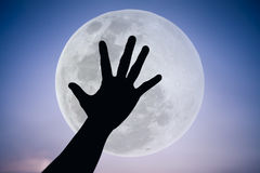 Silhouette of a hand with large full moon on fantastic sky background. Symbol is mean to say hi , five , hand up, stop. Outdoors. Outdoor. Cool colors tone stock images