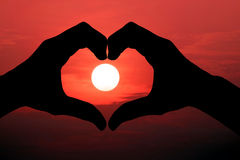 Silhouette of hand made heart symbol across the sun. Stock Photo