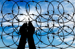 Silhouette of a hand outstretched to the sky. Concept of the refugees. Silhouette of a hand outstretched to the sun in the sky background barbed wire Stock Image