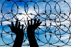 Silhouette of a hand outstretched to the sky. Concept of the refugees. Silhouette of a hand outstretched to the sun in the sky background barbed wire Stock Images