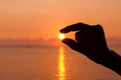 Silhouette hand picking the sun Stock Photo
