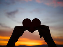 Silhouette hand is raising the red paper heart with blur sunlight during sunset,. Valentines day Royalty Free Stock Photo
