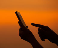 Silhouette of hand using mobile device Stock Images