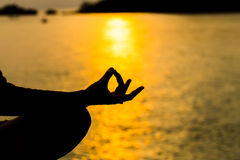 Silhouette, hand of Woman Meditating in Yoga pose or Lotus Posit Stock Photos