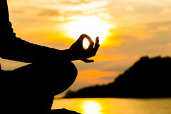 Silhouette, hand of Woman Meditating in Yoga pose or Lotus Posit Stock Photo