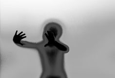 Silhouette and hands behind glass wall Stock Images