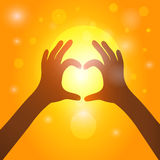 Silhouette hands  in heart shape on background of sunset.  Royalty Free Stock Images