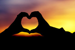 Silhouette of hands heart shaped. A loving create a heart shaped silhouette stock image