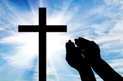 Silhouette of hands outstretched on the cross. Concept of religion. Silhouette of hands outstretched on the cross against a beautiful sky Stock Photo