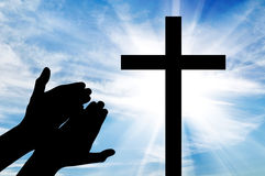 Silhouette of hands outstretched on the cross. Concept of religion. Silhouette of hands outstretched on the cross against a beautiful sky Stock Images