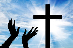 Silhouette of hands outstretched on the cross. Concept of religion. Silhouette of hands outstretched on the cross against a beautiful sky Stock Photography