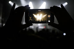 Silhouette of hands recording videos at music concert Stock Photo