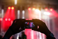 Silhouette of hands with a smartphone at a big music festival Royalty Free Stock Photography