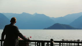 Silhouette of handsome groom watching the mountains and lake view in Como, Italy. Back view stock video footage