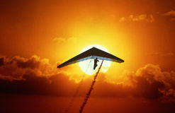 Silhouette of a hang glider at sunset Stock Photo