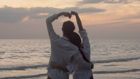 Silhouette of happy asian couple love gesture heart shape symbol of hand on the beach in vacation with romantic together.