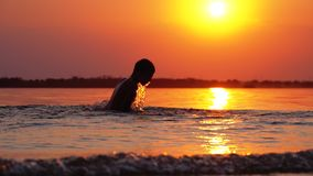 Silhouette of happy boy diving into the river at sunset. Slow motion. Silhouette of happy boy diving into the river at sunset and creating splashes of water stock video footage