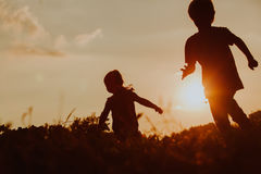 Silhouette of happy boy and girl running at sunset Royalty Free Stock Images