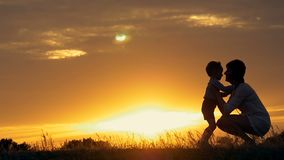 A silhouette of a happy young boy child running into the arms of his loving mother for a hug, in front of the sunset in