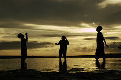 Silhouette happy boys waiting to catch a ball. beautiful sunrise sunset background with dramatic clouds Stock Photography