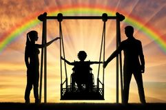 Silhouette of a happy child is a disabled person in a wheelchair on an adaptive swing. Mom and Dad swing it. The concept of the lifestyle of children with stock photo