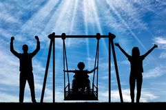 Silhouette of happy child is disabled in a wheelchair on an adaptive swing with mom and dad. have fun together. Concept of the lifestyle of children with royalty free stock image